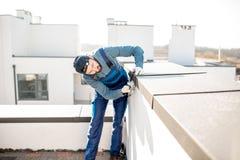 Constructor que monta la cubierta del metal en el parapeto de un nuevo edificio imagen de archivo