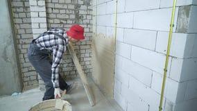 Constructor que nivela el yeso en la pared aireada del bloque de cemento con la regla de la construcción metrajes