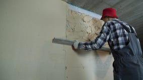 Constructor que nivela el yeso en la pared aireada del bloque de cemento con la regla de la construcción almacen de video
