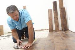 Constructor que pone el suelo de madera Foto de archivo libre de regalías