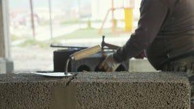 Constructor que trabaja con los bloques de la construcción con la paleta en primero plano almacen de metraje de vídeo