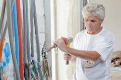 Constructor que usa el martillo y el cincel en la pared imagen de archivo