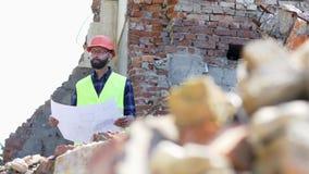 Constructor serio que analiza el dibujo Ingeniero de construcci?n barbudo en casco en fondo constructivo destruido almacen de metraje de vídeo