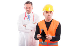 Constructor showing his empty wallet with doctor looking mad Royalty Free Stock Image