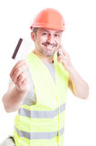 Constructor talking on phone and holding credit card Stock Photos