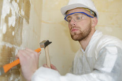 Constructor usando el martillo para quitar el yeso de las paredes imagen de archivo