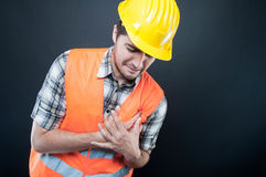 Constructor wearing equipment having heart attack. On black background with copypsace advertising area Royalty Free Stock Photography