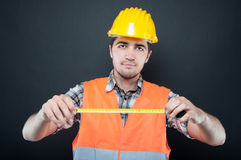 Constructor wearing equipment showing measuring tape. Constructor wearing equipment showing and holding measuring tape on black background Stock Photo