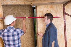 Constructor y arquitecto Inspecting Door Frame Imágenes de archivo libres de regalías