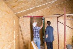 Constructor y arquitecto Inspecting Door Frame Fotos de archivo libres de regalías