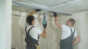 Constructores de sexo masculino usando perfiles de junta de la mampostería seca del metal del taladro eléctrico en emplazamiento  almacen de metraje de vídeo