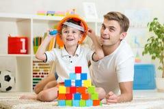 Constructores del juego del muchacho y del padre del niño Imagenes de archivo