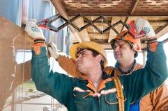 Constructores del trabajador en el azulejo de la fachada Fotos de archivo