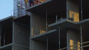 Constructores que construyen el edificio de oficinas de varios pisos en la ciudad, seguridad en el trabajo metrajes