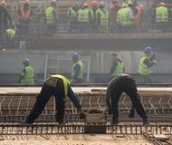Constructores que hacen punto barras de las barras de metal en el refuerzo f del marco Foto de archivo libre de regalías