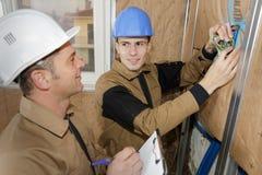 Constructores que instalan el aislamiento termal foto de archivo libre de regalías