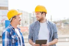 Constructores sonrientes con PC de la tableta al aire libre Imagen de archivo libre de regalías