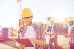Constructores sonrientes en cascos de protección con PC de la tableta foto de archivo libre de regalías