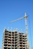 Constructores y del edificio de grúa en emplazamiento de la obra Edificio con dos grúas en emplazamiento de la obra con los const Foto de archivo