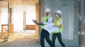 Constructors discussing a plan on a site, side view. stock footage