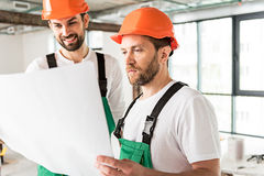 Constructors glancing on necessary plan. Builders are standing in unready apartment and holding drafts. They looking at papers with interest royalty free stock photo