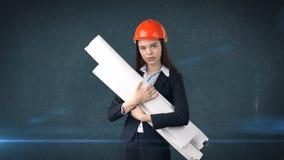 Construindo, conceito tornar-se, de consrtuction e de arquitetura - mulher de negócios no capacete alaranjado com modelo fotografia de stock