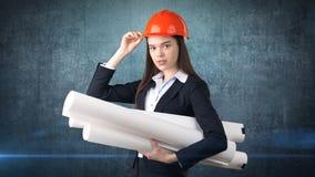 Construindo, conceito tornar-se, de consrtuction e de arquitetura - mulher de negócios no capacete alaranjado com modelo imagem de stock