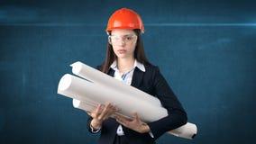Construindo, conceito tornar-se, de consrtuction e de arquitetura - mulher de negócios no capacete alaranjado com vidros e modelo imagens de stock