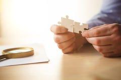 Construindo um sucesso comercial As mãos com enigmas fotografia de stock
