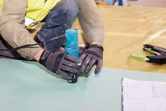 Construindo uma parede para a casa de quadro Ajustador da estratificação do uso do trabalhador para cortar o drywall Fotografia de Stock