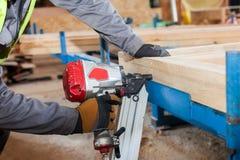 Construindo uma parede para a casa de quadro Nailer de quadro do uso do trabalhador para unir feixes de madeira Imagens de Stock