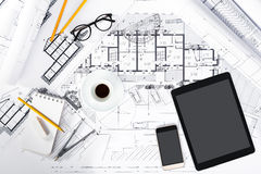 A construção planeia com tabuleta, smartphone e ferramentas de desenho sobre Foto de Stock