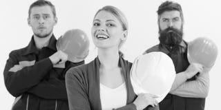 Construtor, arquiteto, coordenador, trabalhador, reparador como a equipe amigável A mulher e os homens guardam capacetes de segur fotos de stock royalty free