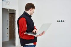 Construtor com o portátil no objeto Imagem de Stock Royalty Free