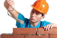 Construtor com a parede da construção da faca de massa de vidraceiro Fotografia de Stock