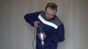 Construtor considerável no uniforme com broca da terra arrendada da correia da ferramenta Homem novo farpado que trabalha com bro filme