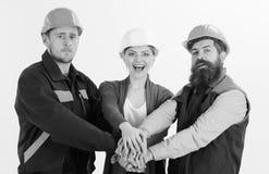 Construtor, coordenador, trabalhador, reparador como a equipe amigável A mulher e os homens nos capacetes de segurança mantêm as  foto de stock royalty free