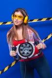 Construtor da menina no capacete da construção e óculos de proteção com uma ferramenta da construção em um fundo azul Foto de Stock