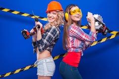 Construtor da menina no capacete da construção e óculos de proteção com uma ferramenta da construção em um fundo azul Fotografia de Stock Royalty Free
