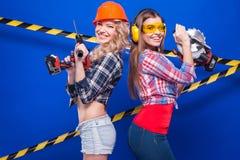 Construtor da menina no capacete da construção e óculos de proteção com uma ferramenta da construção em um fundo azul Imagem de Stock Royalty Free