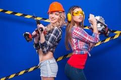 Construtor da menina no capacete da construção e óculos de proteção com uma ferramenta da construção em um fundo azul Fotos de Stock Royalty Free