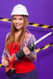 Construtor da menina no capacete da construção e óculos de proteção com uma ferramenta da construção em um fundo azul Fotos de Stock