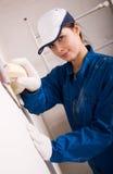 Construtor da mulher nova que lustra a parede Fotografia de Stock