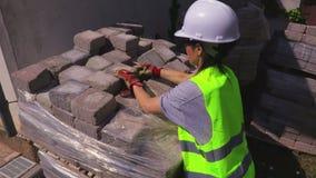 Construtor da mulher que classifica tijolos em exterior video estoque