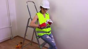 Construtor da mulher que senta-se na escada de etapa vídeos de arquivo