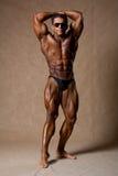 Construtor de corpo masculino atrativo, demonstrando a pose da competição fotografia de stock
