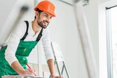 Construtor de sorriso alegre que mantém a pena Imagem de Stock Royalty Free