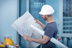 Construtor do arquiteto que estuda o plano da disposição da sala Foto de Stock