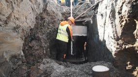 Construtor do tiro da zorra na medida do anel concreto da câmara de visita do capacete de segurança no terreno de construção vídeos de arquivo