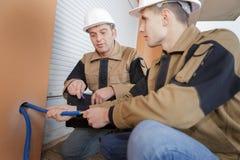 Construtor e encanador que trabalham com as tubulações de água na sala de caldeira foto de stock